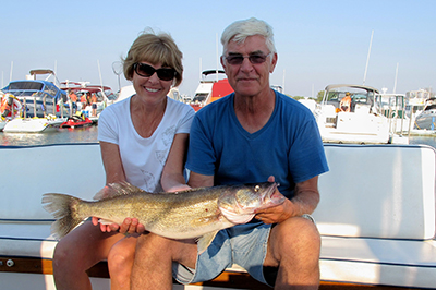 Two anglers are all smiles as they show off a large walleye caught in western Lake Erie.